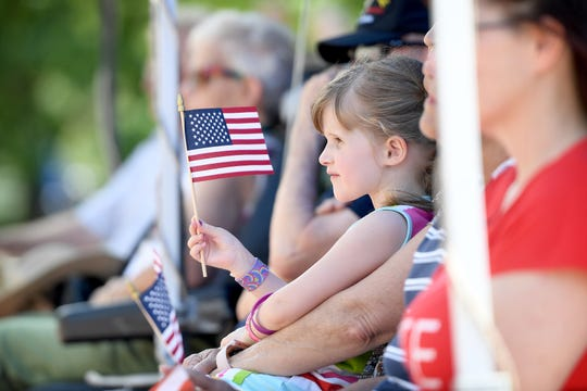 Adelaide Neilans, 4, waves a tiny American flag during the Asheville, N.C., Memorial Day ceremony.