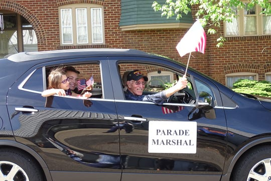 Parade marshal Richard Schmidt and his family members wave during the Bucyrus Memorial Day parade.