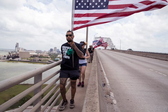 A group of veterans and supporters from the nonprofit gym Project MMA walk over the Harbor Bridge on Monday, May 27, 2019 in observance of Memorial Day. It isn't the first time the group has walked the bridge carrying flags. For the last three years they've walked the bridge every Memorial Day, Veterans Day and Armed Forces Day. They also walk the bridge on the 22nd of every month to remember the 22 veterans who were lost to suicide every day in 2013. The number has since fallen to 20 per day.