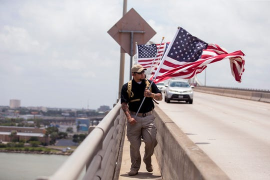 Michael Goss leads a group of veterans and supporters from the nonprofit gym Project MMA as they walk over the Harbor Bridge on Monday, May 27, 2019 in observance of Memorial Day. It isn't the first time the group has walked the bridge carrying flags. For the last three years they've walked the bridge every Memorial Day, Veterans Day and Armed Forces Day. They also walk the bridge on the 22nd of every month to remember the 22 veterans who were lost to suicide every day in 2013. The number has since fallen to 20 per day.
