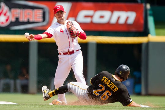 Cincinnati Reds shortstop Jose Iglesias (4) turns a double play as Pittsburgh Pirates second baseman Adam Frazier (26) slides into second in the fifth inning of the MLB National League game between Cincinnati Reds and Pittsburgh Pirates at Great American Ball Park in Cincinnati on Monday, May 27, 2019.