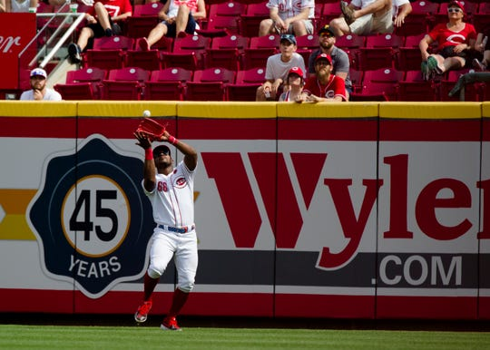 Cincinnati Reds right fielder Yasiel Puig (66) catches a pop fly in the eighth inning of the MLB National League game between Cincinnati Reds and Pittsburgh Pirates at Great American Ball Park in Cincinnati on Monday, May 27, 2019.