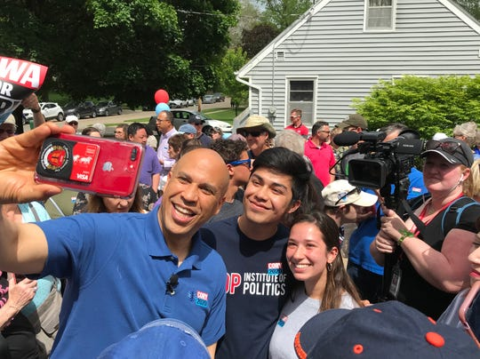 Sen. Cory Booker takes a selfie photo with fans at an Urbandale barbecue that drew more than 500 people to his campaign headquarters on Monday, May 27, 2019.