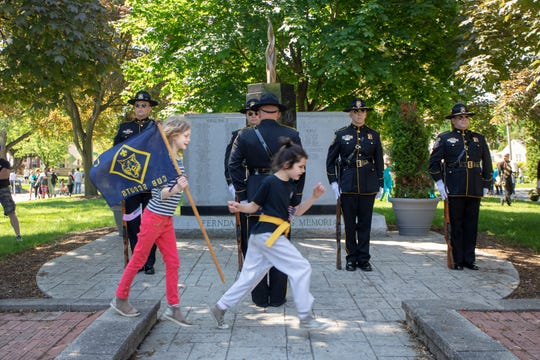 L to R:  Sabine Jungmann, 8 and Madeline Walgters, 8 of Ferndale play in front of the the Ferndale Police Honor Guard at the the Ferndale Memorial Mall in Ferndale, Mich., Sunday, May 27, 2019.