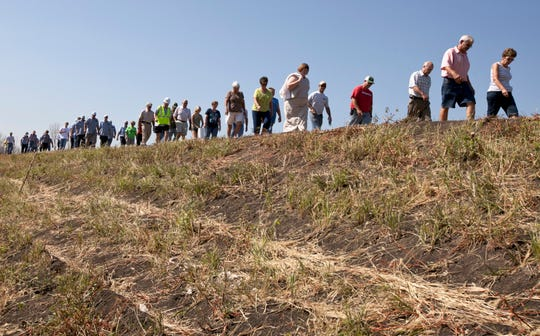 In this July 26, 2012, file photo, residents of Hamburg, Iowa, in a show of support, walk on the levee the town built the previous year to protect it from the Missouri River flood.