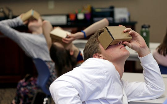 In this photo taken Tuesday, May 21, 2019, photo, Zane Taylor and other students use virtual reality technology to learn about the D-Day invasion at Normandy during a history class at Crossroads FLEX school in Cary, N.C.