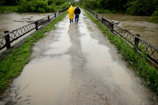 In this photo taken May 21, 2019, Robert Collins, left, and Bobby Joe Branston watch rising waters in the Fishing River from a condemned bridge in the small community of Mosby, Mo.