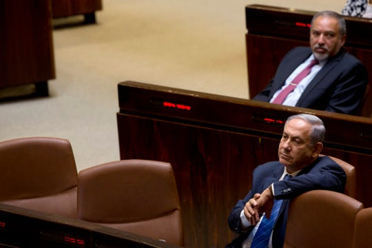 In this May 23, 2016 file photo, Israeli Prime Minister Benjamin Netanyahu and former Israeli Defense Minister Avigdor Lieberman sit in the Knesset, Israel's parliament, in Jerusalem.