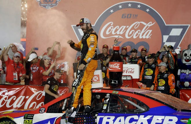 Martin Truex Jr. celebrates in Victory Lane after winning the NASCAR Cup Series race at Charlotte Motor Speedway.