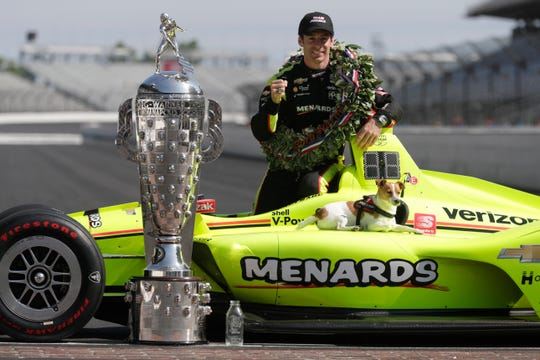 Simon Pagenaud poses with his dog Norman during the traditional winner's photo session at the Indianapolis Motor Speedway on Monday.