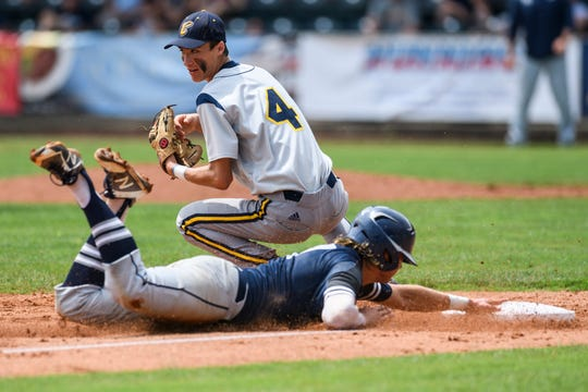 Reitz's Ryan Kassel (17) safety slides into third case as Castle's CJ Backer (4) misses a catch during the second inning of the IHSAA Class 4A sectional championship at Bosse Field in Evansville, Ind., Monday, May 27, 2019. The Knights defeated the Panthers 14-2 in five innings to claim the sectional title.