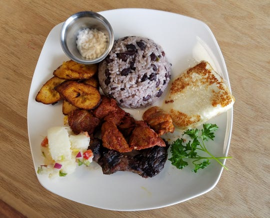A plate from Tipico with gallopinto, fried fresh cheese, pork in achiote, carne asada, yuca salad and fried plantains with a side of mayonnaise.