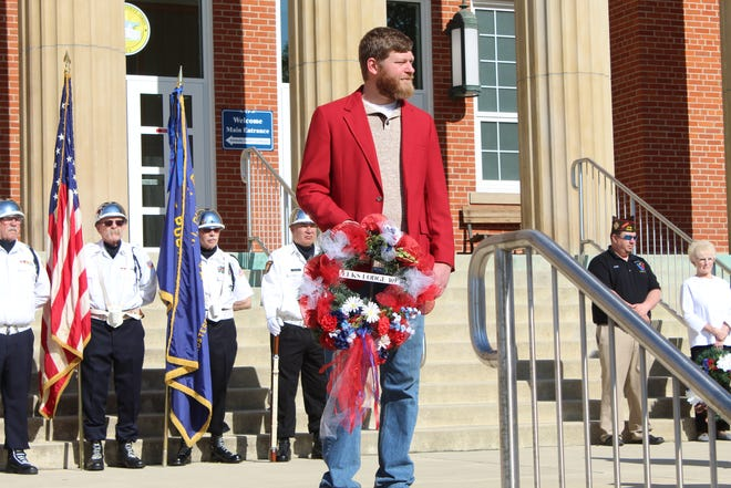 Lee Celek of Fremont's Elks Lodge 169 holds a ceremonial wreath on the Sandusky County Courthouse steps Monday, as the community honored fallen veterans at a Memorial Day ceremony.