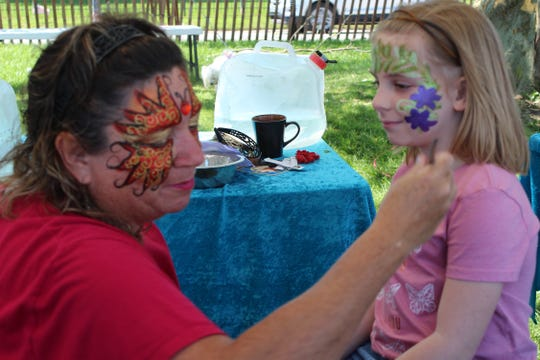 Dawn Gurtner of A Splash of Sunshine paints the face of Lilly Noggle, 6, of Port Clinton Monday at the 39th annual Main Street Port Clinton Walleye Festival. Organizers said thousands of visitors came to the festival over Memorial Day weekend.
