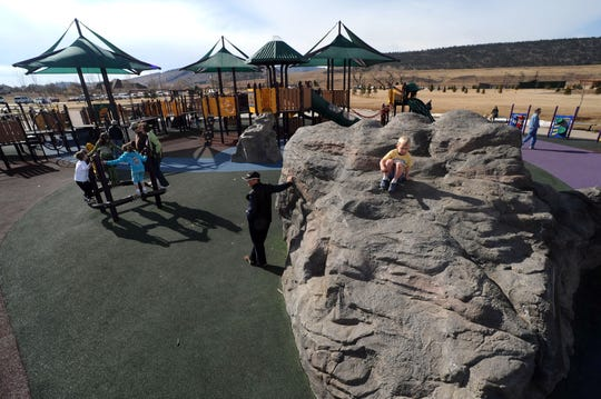 A giant rock is part of the playground at Inspiration Playground at Spring Canyon Community Park.