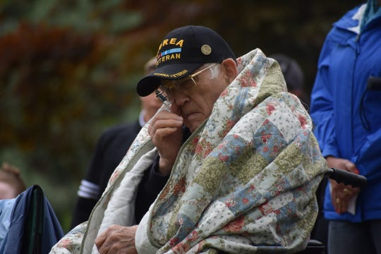 A Korean War veteran wipes a tear from his eye during the Memorial Day ceremony at Grandview Cemetery on Monday.