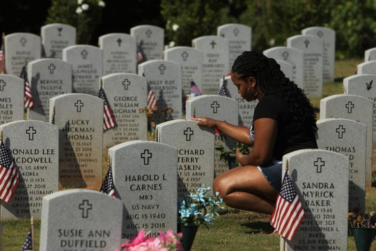 "Latasha Baskin grieves beside her father's tombstone at M.J. ""Dolly"" Cooper Veterans Cemetery."
