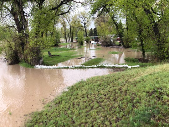 The Sun River flows out of its banks in the Sun River Valley Monday.