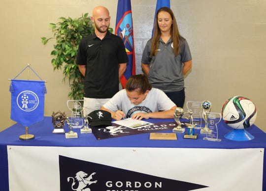 Harvest Christian Academy Girls Soccer Head Coach Jeremy Wendal, left, and  and Guam U19 Women's National Team Head Coach Maggie Phillips observe as Sabrina Kenney officially signs to play women's soccer for Gordon College in Massachusetts during a signing ceremony at the Guam Football Association National Training Center.
