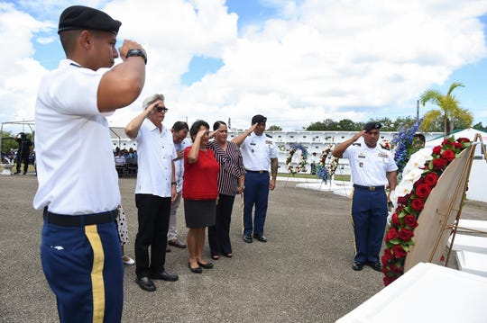 Gov. Lou Leon Guerrero, center, and Speaker Tina Muna Barnes salute during a wreath presentation dedicated to the Tomb of the Unknowns during the Memorial Day Commemoration at the Guam Veterans Cemetery in Piti, May 27, 2019.