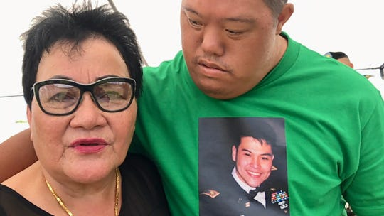 Talofofo resident Agnes San Nicolas Rillera, left, talks about her late son, U.S. Army Major Henry San Nicolas Ofeciar, whose picture is on the shirt of one of his cousins, Quentin San Nicolas, during the Memorial Day commemoration on Aug. 27, 2019 at the Guam Veterans Cemetery in Piti.