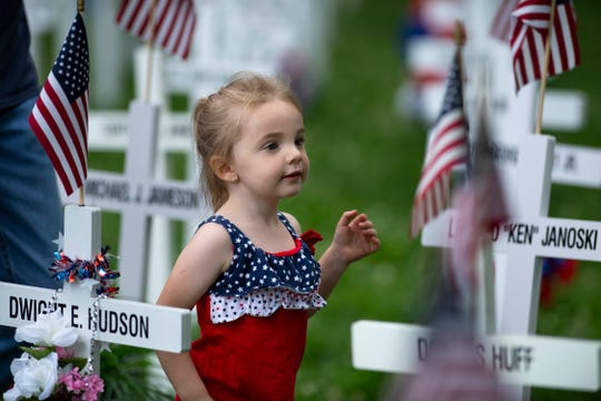 Maci Mae Lawton, 3, searches with her family for the marker of her great grandfather Latham Barnam LB Lawton at Henderson's Central Park during Memorial Day services Monday morning.