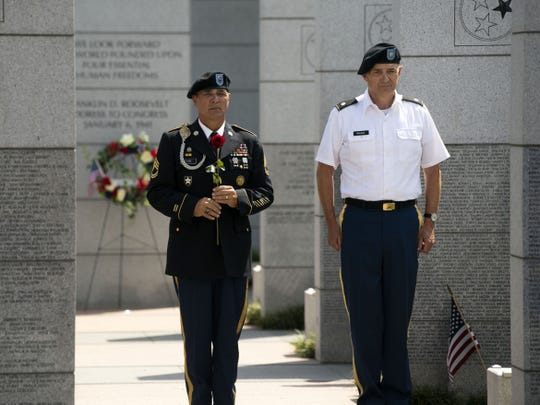 U.S. Army veterans Don Plane, left, of the American Legion Post 2, and Logan Hickman, of the East Tennessee Veterans Memorial Association, place roses for four new names added to the East Tennessee Veterans Memorial on Monday.