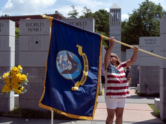 Army veteran Vickie Plane of American Legion Post 2 furls a Navy flag after the Memorial Day ceremony at the East Tennessee Veterans Memorial on Monday.