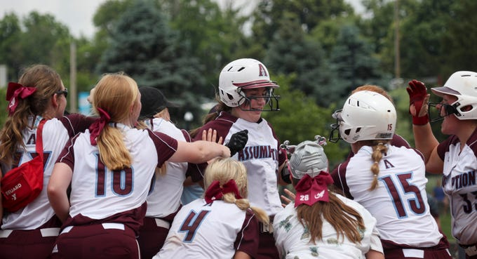 Assumption's Olivia Pastin celebrates with her team after hitting a home run against Ballard in the  KHSAA 7th Region semi-final game on May 27.
