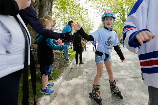 The Manitowoc County Youth Hockey Association gives out high fives during the Memorial Day parade Monday, May 27, 2019, in Manitowoc, Wis.