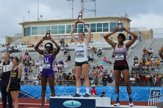 Galion graduate Marisa Gwinner raises her national championship hardware from atop the podium after winning an NCAA Division II national championship in the high jump as a freshman for Tiffin University.