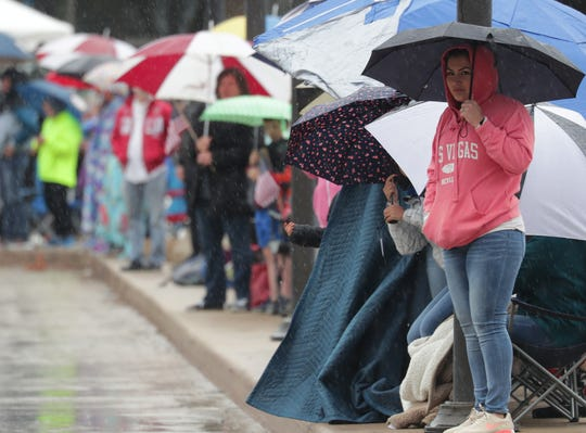 As a steady rain falls, people watch from under umbrellas during Milwaukee's 154th annual Memorial Day Parade.