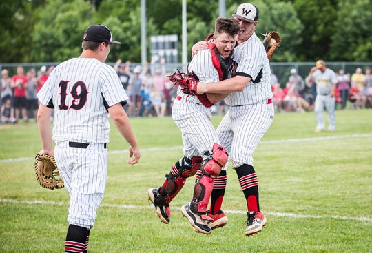 Wapahani's Tysen Lipscomb and Brevans Rivers celebrate after catching the game-winning out against Monroe Central during their sectional championship game at Lapel High School Monday, May 27, 2019.