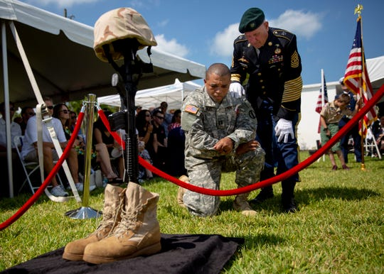 Command Sgt. Maj. James Burch stands over Capt. Torrey Searles as he kneels next to a display remembering fallen soldiers during a Memorial Day ceremony at Hodges Funeral Home at Naples Memorial Gardens on Monday, May 27, 2019.