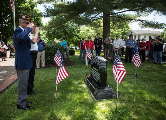 Marine Buck Hopkins and Jim Haskins from the United States Air Force salute a memorial at Veterans Park in Newark after unveiling the stone at a Memorial Day service.