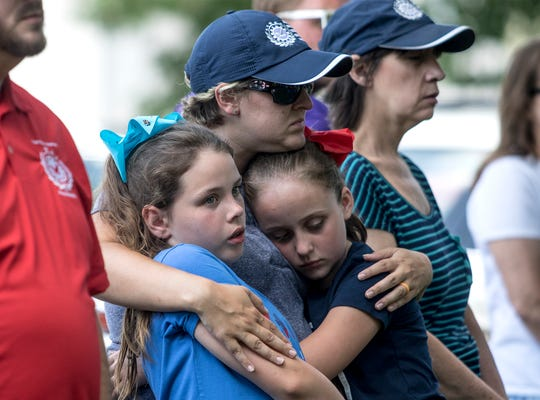 April Foster, Director of the Veterans Service Office in Licking County hugs her daughter Hannah (right) and her best friend, Caitlyn Bowen. During a dedication to a memorial for veterans at the Veteran Park on 6th Street in Newark. Bowman's father is currently serving in Iraq.