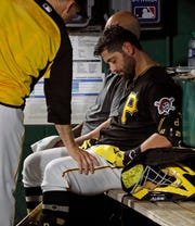 Former New York Yankees and current Pittsburgh Pirates catcher Francisco Cervelli is consoled by hitting coach Rick Eckstein, left, after taking himself out of a baseball game against the Los Angeles Dodgers during the fourth inning in Pittsburgh, Saturday, May 25, 2019. Cervelli had been hit in the head by a foul tip in the top of the inning.