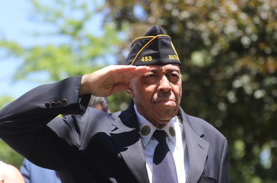 """American Legion Post 453 Commander, Charles Gunn, stands at attention during the playing of """"Taps"""" in front of the Laval brothers former home in Rutherford.  Monday, May 27, 2019"""