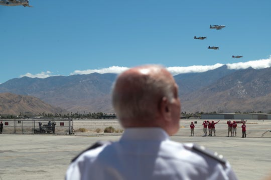 A civil air patrol member watches planes fly over head at the Palm Springs Air Museum's Memorial Day flower drop and air fair, Palm Springs, Calif., May 27, 2019.