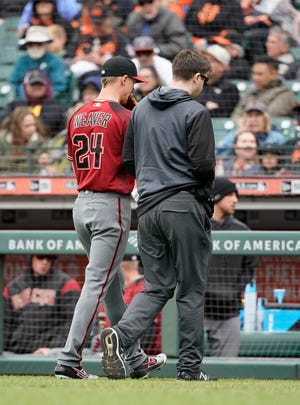 Diamondbacks pitcher Luke Weaver (left) walks off the field with a trainer during the sixth inning against the Giants on Sunday.