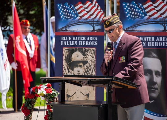 Dan Crocker, a retired state director of veterans services, delivers remarks during the annual Memorial Day ceremony Monday, May 27, 2019 at Pine Grove Park in Port Huron. Several prototype banners bearing the names and faces of St. Clair County veterans, organized by the Blue Water Area Fallen Heroes Community Banner Program, are lined up behind him.