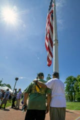 """Elwood """"Woody"""" Rice, left, gets a hug from Eric Kirkland beneath the flag dedicated to Calvin C. Rice Jr. at Penn Park on Memorial Day. Kirkland was a friend of Calvin Rice, who was killed in action during the Vietnam War."""