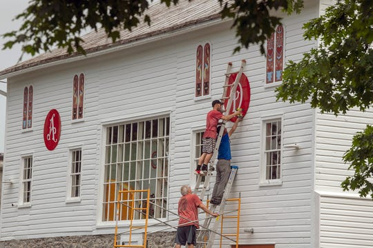 From the top, Greg Koller, Joe Bowser and Bruce Koller install the second letter for American Daydream Antiques & Miscellanea, which will open June 1 after a seven-month restoration project of the old barn.