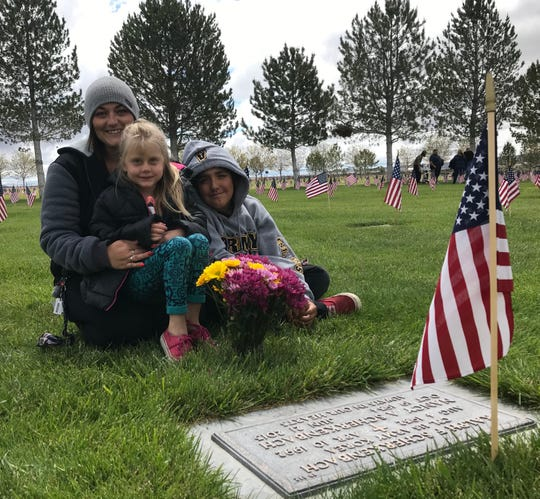 Ashley Scherkenbach and her children, Madie and Zach, visit the grave of her grandparents at the Northern Nevada Veterans Memorial Cemetery.