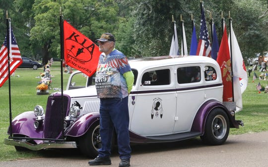 """Fred Loveland watches a Memorial Day observance Monday at Redding Memorial Park next to his decorated """"Wounded at War"""" 1934 Ford. Loveland is a member of the Patriot Guard Riders who attend funeral services of veterans."""