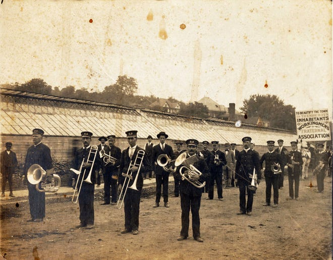 """Recently discovered, never-before-published photo of the Workingmen's Fraternal Association marching with a band on Central Avenue. The sign reads, """"To beautify the town is to enrich its inhabitants."""" The greenhouses shown here were those of longtime businessman John Fallon; they stood at about where the parking lot of today's Howard Johnson is located. The houses in the background were on Lewis Street."""