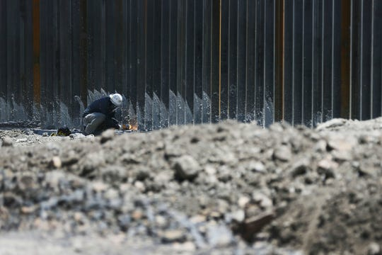 "Workers work on a wall being built by Monument One, an official marker at the spot where New Mexico, Texas and the Mexican state of Chihuahua converge, by Border Highway West, near Executive Center Boulevard Monday, May 27, by ""We Build the Wall"" organization on land owned by American Eagle Brick Company."