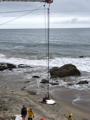 Ventura County firefighters rescued a hang glider from rocks along Pacific Coast Highway Sunday afternoon in an incident that closed lanes for a time.