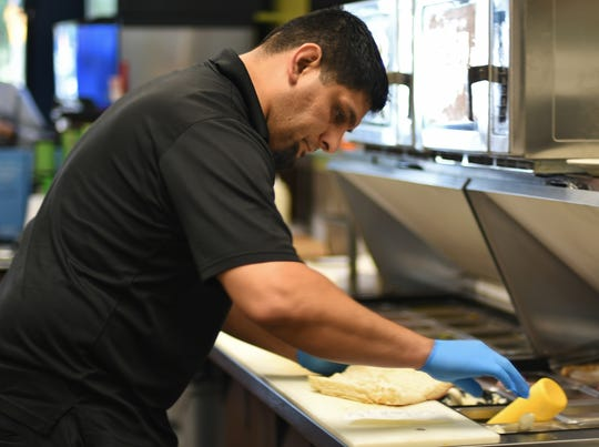 "Nick Huerta prepares a sandwich at Deli Delicious in Visalia on Mooney Boulevard. Dozens of franchisees, including Huerta, formed the Delicious Franchisee Association earlier this year to push back against the Fresno-based chain's ""lack of transparency"" and ""predatory tactics,"" he said."