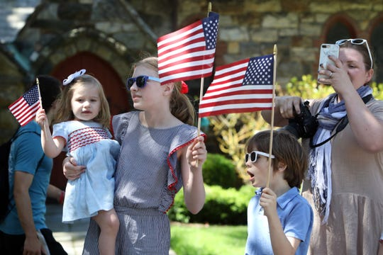 Spectators waves flags as they watch the Town of New Castle Memorial Day Parade in Chappaqua, N.Y. May 27, 2019.